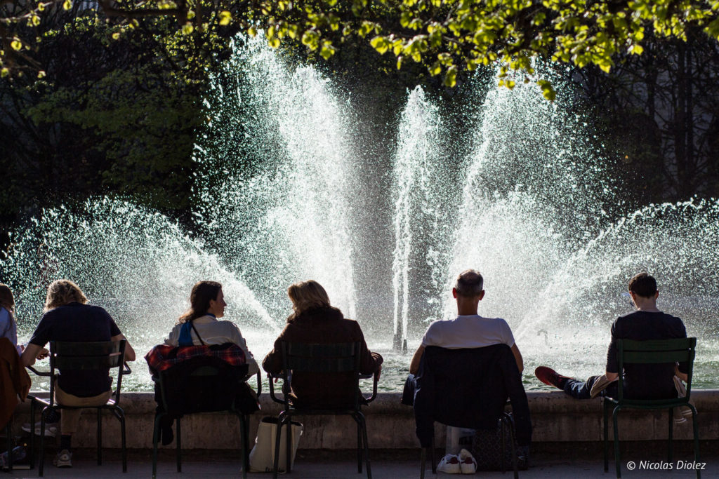 gens assis devant une fontaine Paris été